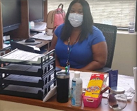 woman at her desk with a mask on