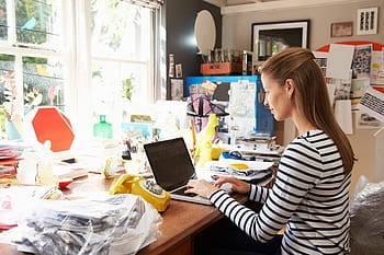 Woman working from home, seated at desk with laptop