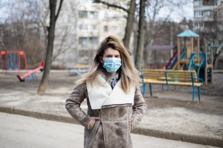 Woman standing in front of playground, wearing a medical mask