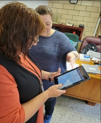 Two women looking at a mobile device tablet